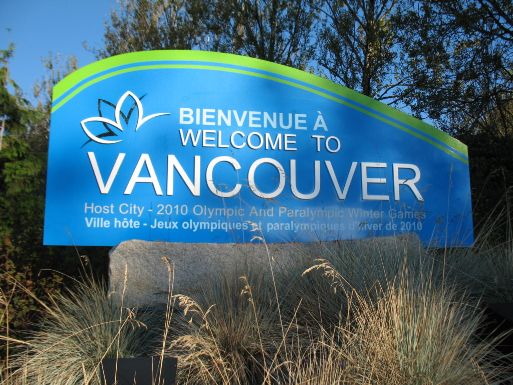 welcome to vancouver sign surrounded by ornamental grass and trees